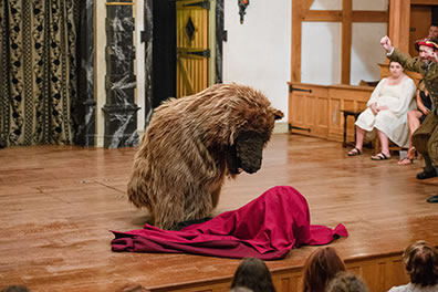 Production photo by Marek K. Photography of the bear sniffing at the blanketed baby with Antigonus on the right side waving his arms.