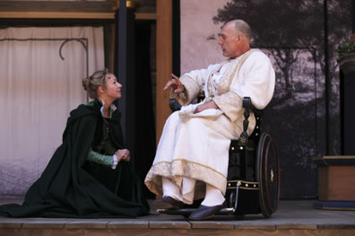 Helen in black overcoat kneels to the king dressed in a white robe and sitting in a wheelchair