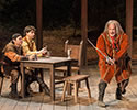 Production photo of Falstaff weilding a bent, hacked swoard as Poins and Hal sit at a table watching.